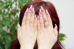 Hands on the face. Female hands on the face with beautiful manicure Stock Image