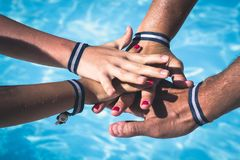 Hands of family of four with all inclusive wrist bands. Family team with bracelets by swimming pool, summer vacation, holiday resort, parents and kids hotel royalty free stock photo