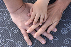 Hands of a family lying on each other on a grey table Royalty Free Stock Photos