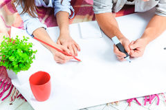 The hands of  family  at repair and relocation. The family planing  to accommodation on a floor Stock Image