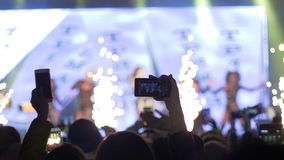 Hands of fans with mobile phones make photo and video recording at rock festival in scene lights in evening. Hands of fans with mobile phones make photo and stock video