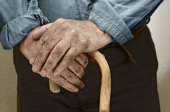 Hands of farmer. Peasant hands, leaning on a cane placed in front of him Royalty Free Stock Image