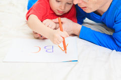 Hands of father and child writing letters Royalty Free Stock Photos