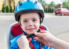 Hands of father putting biking helmet on to his son. Stock Photo
