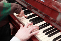 Hands of father and son playing on brown piano Stock Images