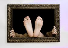 Hands and feet in a frame. Woman hand and feet try to exit from a painting frame stock images