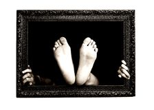 Hands and feet in a frame. Woman hand and feet try to exit from a painting frame Stock Photo