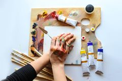 Hands of female artist on the messy dirty palette with different royalty free stock photo