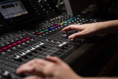 Hands of female audio engineer using sound mixer Stock Photo
