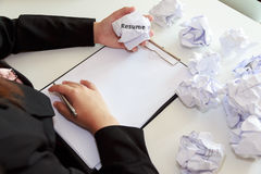Hands of female crumple sheets of Resume at the desk, mistake re Royalty Free Stock Photography