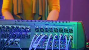 Hands of a female DJ behind a mixing console in the light of a disco. The average plan stock video