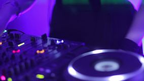 Hands of female dj turning controls on professional sound equipment in nightclub. Stock footage stock footage