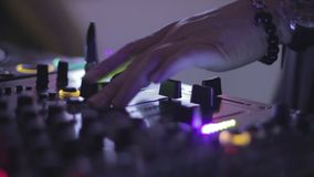 Hands of female Dj tweak and move turntable and mixer in the nightclub. Stock footage stock video footage