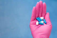 Hands of female doctor in pink glove with pile of pills of diffe. Rent color. Legal drug store concept Royalty Free Stock Images