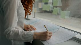 Hands of female financial analytic in white shirt working with printed graphs. Using pensil near the window in the office. Indoors stock video footage