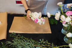 Hands of female florist creating bouquet on black table Stock Photos