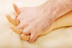 Hands of female and male lying on bed. Stock Photos