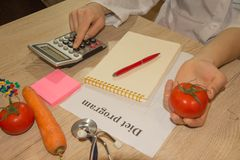 Hands of female nutritionist counting calories in hospital. Fresh vegetables and fruit, measuring tape with diet plan Royalty Free Stock Photos