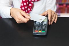 Hands of a female shop assistant holding a credit card and makin stock photography