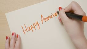 Hands of a female student with red nails writing happy anniversary on a blank paper with red marker -. Hands of a female student with red nails writing happy stock video footage
