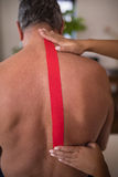 Hands of female therapist applying elastic therapeutic tape on shirtless senior male patient back Royalty Free Stock Image