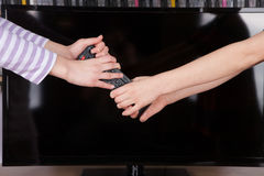Hands fighting for the remote control in front of the TV screen Royalty Free Stock Images