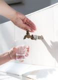 Hands filling water plastic cup. Royalty Free Stock Image