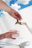 Hands filling water plastic cup. Hands filling mineral water plastic cup Royalty Free Stock Images
