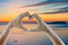 Hands and fingers in heart shape framing setting sun at sunrise twilight sky over ocean sea. In summer. Summer background colorful concept Stock Photos