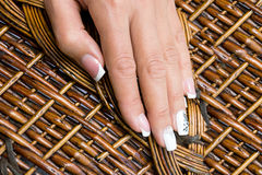 Hands fingers manicure. On a wicker basket Royalty Free Stock Images