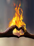 Hands with fire in form of heart stock photography