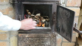 Hands fire newspaper paper firewood with match old rural stove stock video footage