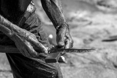 Hands of a fisherman with a knife. Royalty Free Stock Photos
