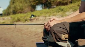 Hands fisherman sitting on chair by river nearly fishing rod waiting for bite. Man hobby summer fishing on river in sunny day stock footage