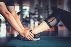 Hands of fitness trainer grab at fitness woman legs to training stock photo