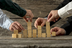 Hands of five businessman holding wooden blocks placing them int Stock Photography