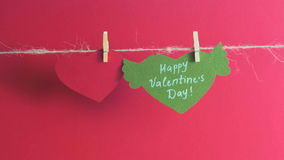 Hands fixing a paper heart with congratulation and wings with a clothespin near a red heart on a cord. Red background. stock footage