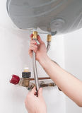 Hands fixing the plumbing pipes of an electric boiler. Stock Photography