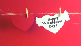 Hands fixing a white heart with congratulation and wings fixed with clothespin on a cord. Red background. stock footage