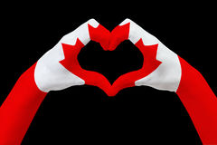 Hands flag of Canada, shape a heart. Concept of country symbol, isolated on black. Stock Image