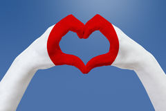 Hands flag of Japan, shape a heart. Concept of country symbol, on blue sky. Stock Images
