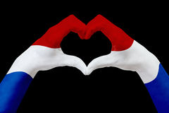 Hands flag of Netherlands, shape a heart. Concept of country symbol, isolated on black. Royalty Free Stock Photo
