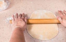 Hands flatten sheet of dough by wooden rolling pin. Cooking of pie - hands flatten sheet of dough by wooden rolling pin stock image