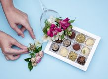 The hands of the florist decorate with flowers a box of chocolates handmade from white chocolate and pistachios stock image