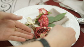 Hands florist decorate the white plate quarter red garnet. On the white dishes lies a napkin, on which lies a pink, blooming rose with green leaves. During stock footage