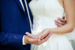 Hands with flying golden  rings. Bride's and groom's hands with flying rings Stock Photo