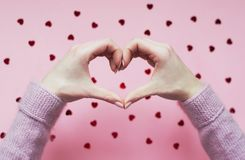 Hands folded heart on pink background with red hearts. stock photography