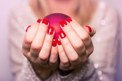 Hands folded holding the Christmas ball Stock Images