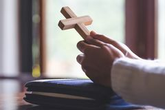 Hands folded in prayer on a Holy Bible in church concept for fa stock photography