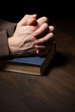 Hands folded in prayer over a Holy Bible Stock Photos